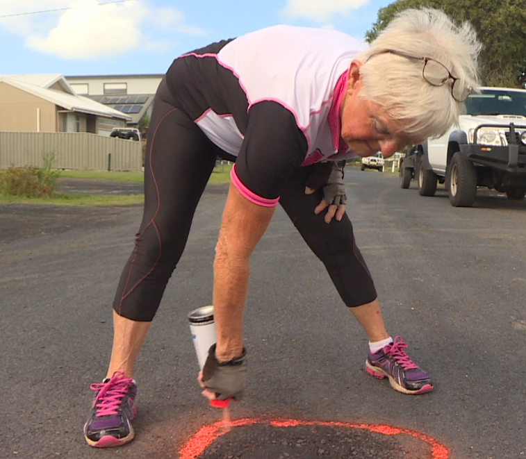 74 YEAR OLD LADY SPRAY PAINTING A BRIGHT ORANGE CIRCLE AROUND A POTHOLE